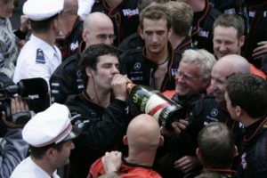 Marc Priestley takes a swig of the bubbly with his colleagues waiting and Kimi Raikkonen (top left) watching with a smile